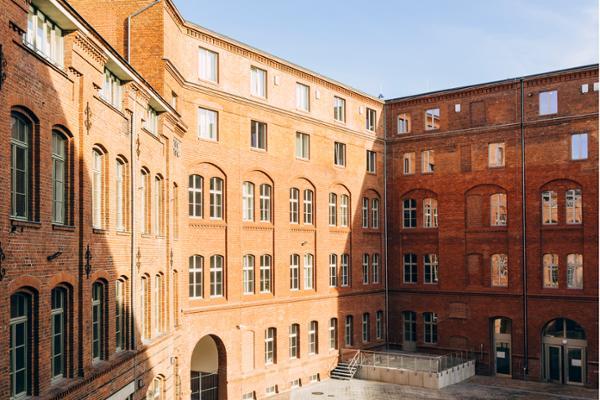 Ein Blick auf das rote Backsteingebäude und den Innenhof der Zentralen Zulagenstelle für Altersvermögen am Standort Brandenburg an der Havel.
