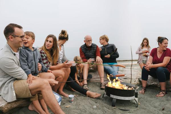 Eine Gruppe Menschen unterschiedlichen Alters sitzt am Strand im Halbkreis um ein Lagerfeuer herum.