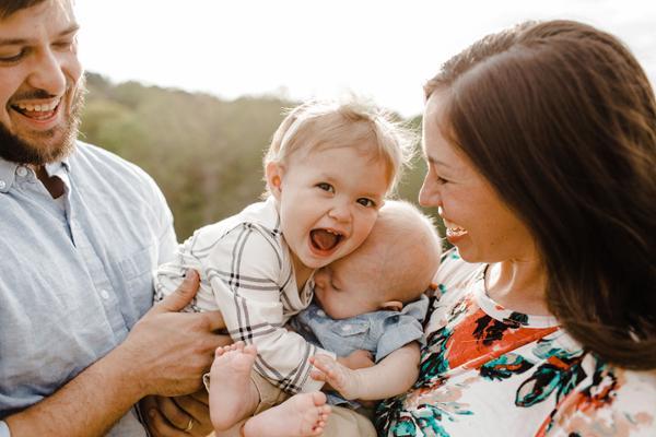 Eine Frau und ein Mann halten zwei Kleinkinder im Arm und lachen.