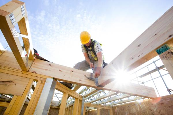 Ein Handwerker mit gelbem Helm baut an dem Dachstuhl eines neu gebauten Hauses.