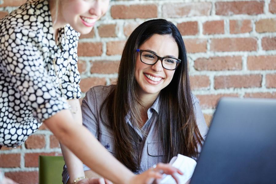 Eine Frau sitzt vor einem Laptop und bekommt von einer anderen Frau etwas auf dem Bildschirm gezeigt.
