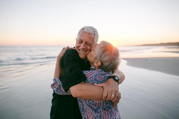 Bei Sonnenuntergang am Strand küsst eine ältere Frau einen älteren Mann auf die Wange.