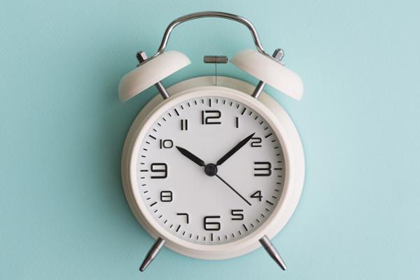 Ein weißer Wecker vor blauem Hintergrund zeigt die Uhrzeit 10:08 Uhr.