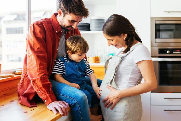Ein Mann und ein kleiner Junge sitzen auf der Arbeitsplatte in der Küche und betrachten den Bauch einer schwangeren Frau, die vor ihnen steht.