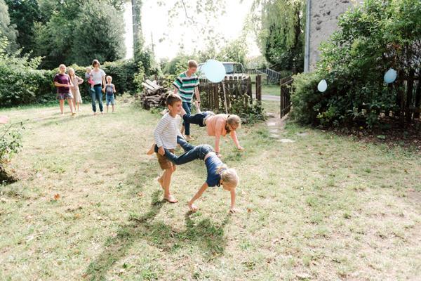 Eine Frau und mehrere Kinder verschiedenen Alters spielen im Garten.