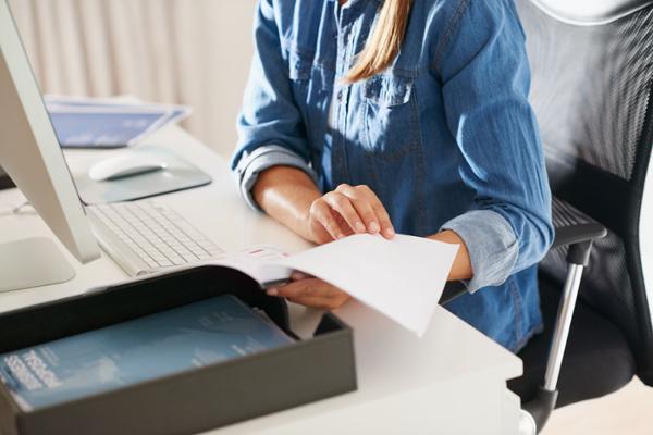 Eine Person sitzt vor einem Computer am Schreibtisch und blättert in Unterlagen.