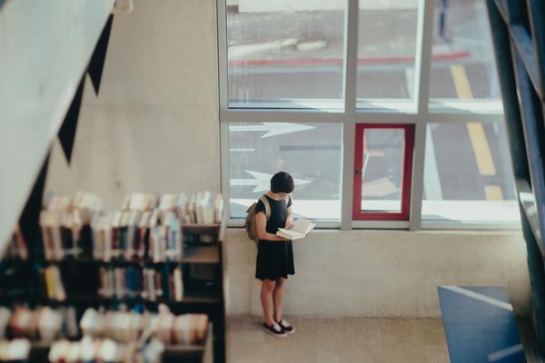 Eine Frau steht am Fenster in einer Bibliothek. Sie hält ein aufgeschlagenes Buch in den Händen.
