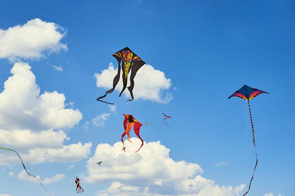 Mehrere bunte Lenkdrachen fliegen am blauen Himmel mit weißen Wolken.
