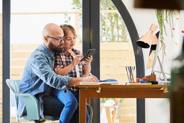 Vor einem Schreibtisch sitzt ein Kind auf dem Schoß eines Mannes mit Bart, Glatze und Brille. Das Kind beschäftigt sich mit einem Taschenrechner, der Mann schreibt in ein Notizbuch.
