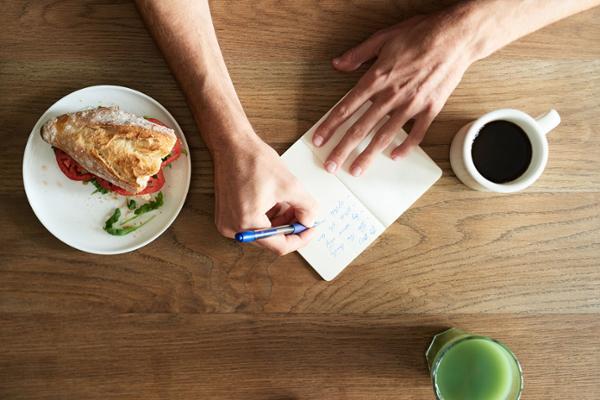 Eine Tischplatte aus der Vogelperspektive, in der Mitte zwei Hände. Die eine schreibt etwas in ein Notizbuch, die andere hält das Buch, drumherum stehen ein Teller mit einem belegten Brötchen, eine Tasse Kaffee und ein Glas Saft.
