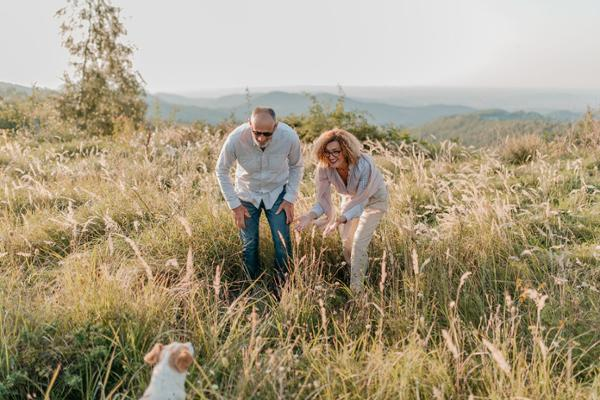 Eine Frau und ein Mann spielen auf einer Wiese mit einem Hund.