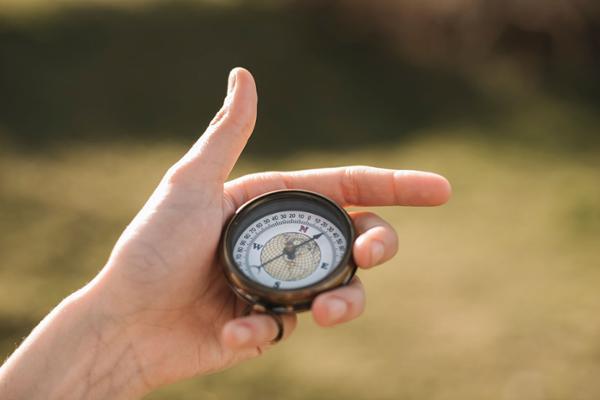 Eine linke Hand, die einen Kompass hält.