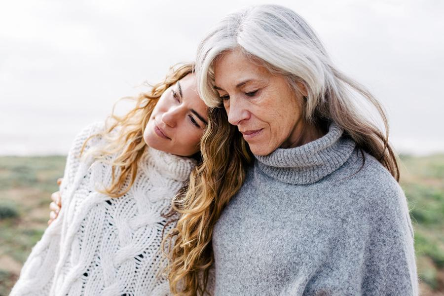 Eine ältere Frau hält eine jüngere Frau im Arm, die jüngere legt der älteren den Kopf auf die Schulter.