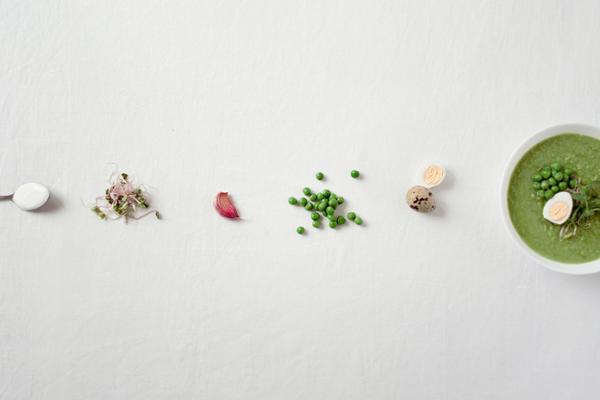 Nebeneinander aufgereiht von links nach rechts: ein Teelöffel mit Salz, Sprossen, eine Knoblauchzehe, grüne Erbsen, ein Wachtelei und eine Schale Erbsensuppe.