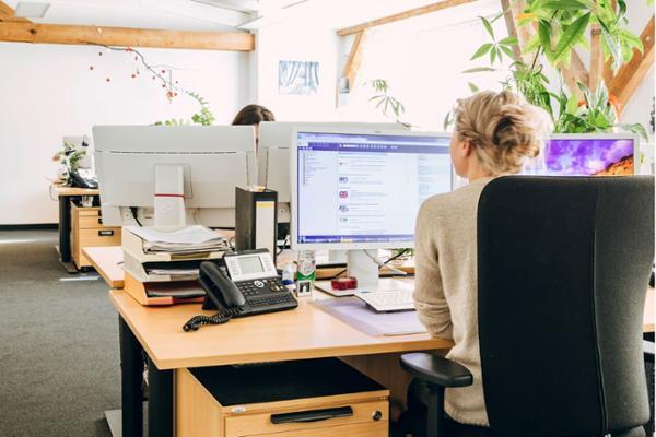 Eine Mitarbeiterin der Zentralen Zulagenstelle für Altersvermögen sitzt im Büro am Schreibtisch vor einem Computer.