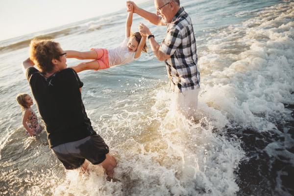 Eine Frau und ein Mann mittleren Alters spielen mit zwei Mädchen in kniehohen Wellen.