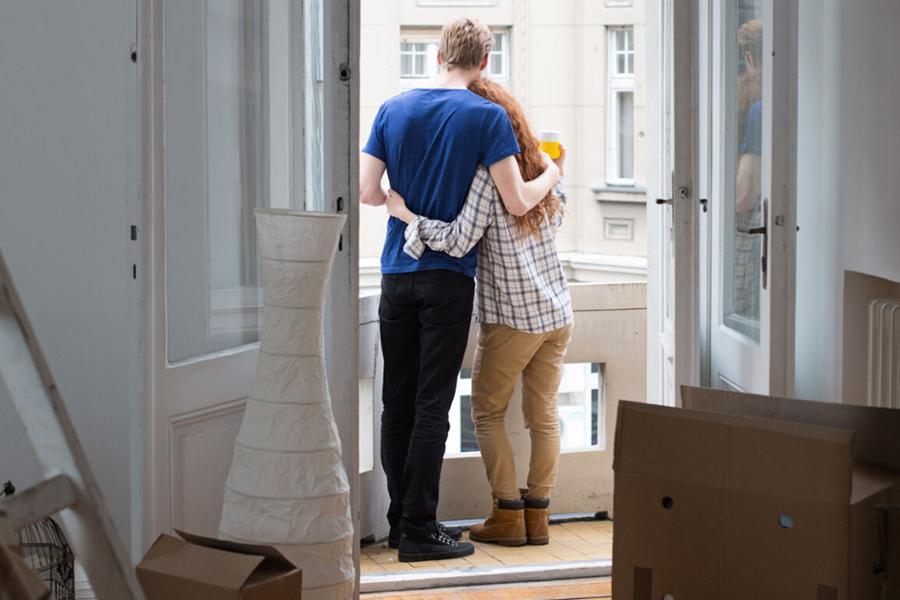 Aus einem Zimmer voller Umzugskarton sieht man auf dem dazugehörigen Balkon eine Frau und ein Mann, die sich umarmen.