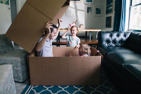 Ein Mann und ein Kleinkind sitzen in einem großen Pappkarton, daneben steht ein kleines Mädchen, alle drei lachen.